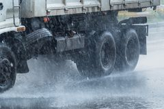 Rainwater spraying from motion truck wheels. city road during he Stock Image