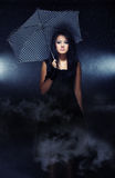 Rainy. Elegant lady with umbrella standing under the rain Royalty Free Stock Photography