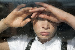 Rainy. The girl looks out of the window rainy day Royalty Free Stock Photography