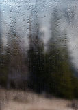 Rainy autumn landscape through a window with raindrops. Royalty Free Stock Images
