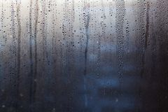 Flowing down water drops on window glass Royalty Free Stock Photo