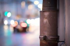 Rainy city scenery: Rain drain and city lights in the background. Closeup of rain drain, urban city lights in the blurry background life evening dusk blurred royalty free stock photos