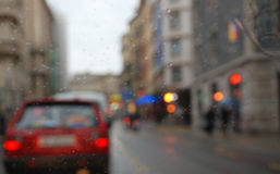 Rainy city scenery through wet windscreen Royalty Free Stock Photography