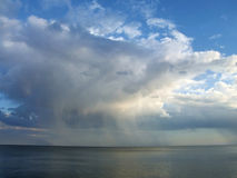 Rainy cloud. Seascape - big white rainy cloud over the calm sea stock photo