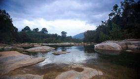 Rainy Clouds Motion over River between Rocky Banks in Vietnam. Dark grey rainy clouds motion over tropical forest river among round rocky banks in Vietnam stock video footage
