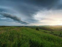 Rainy clouds over green mountains. Rain clouds during sunset over green mountains Stock Images