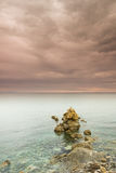 Rainy coastal landscape. Vertical gloomy landscape with the rocky beach in the foreground. Picture was taken on the eastern coast of Holy mount Athos, Greece Royalty Free Stock Photography