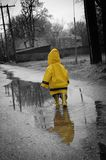 Rainy Day. Child spalsing in puddles on a dready day, selective color Stock Photo