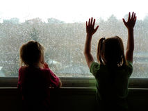Rainy Day. Two little kids looking out window on rainy day Stock Images