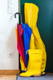 Rainy day. Yellow raincoat, rubberboots and colorful umbrella royalty free stock photo