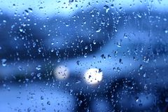 Rainy day. Car with headlights is seen through a rain spattered window stock photo
