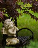 Rainy Day Angel. Angel or cupid figure praying on a bench under a Japanese Maple tree on a rainy day Royalty Free Stock Photography
