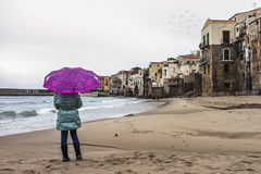 A rainy day at the beach. A girl with an open umbrella protecting herself from the rain The shot was taken in Cefalu, Sicily royalty free stock photos