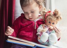 A rainy day is best for reading with your favorite doll stock photo