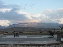 Rainy Day Blackhawks. Low rain clouds over the northern Hindu Kush mountains. UH-60 Blackhawks sitting on the flight line at Mazar-I-Sharif, Afghanistan stock photo