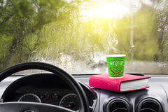 Rainy day in the car window with a glass of hot coffee and a book Stock Photo