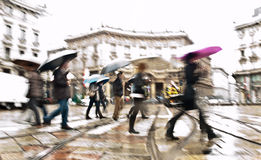 Rainy day in the city. Intentionally motion blurred abstract image of commuters in a european city in a rainy day. Shot in Milan, Italy Stock Image