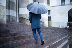 Man walking in the city with umbrella on rainy day Royalty Free Stock Images