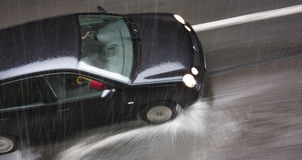 Rainy day in the city: A driving car in the street hit by the he Royalty Free Stock Image