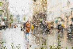 Rainy day in city. People seen through raindrops on glass. Selective focus on the raindrops. Silhouette of girl in bright beautiful coat royalty free stock photo