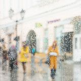 Rainy day in city. People seen through raindrops of window. Selective focus on raindrops. Silhouettes of girls in bright. Rainy day in city. People seen through Stock Photos