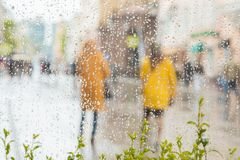 Rainy day in city. People seen through raindrops of window. Selective focus on raindrops. Silhouettes of girls in bright. Rainy day in city. People seen through Stock Images