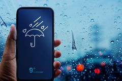 Rainy Day Concept. Hand Holding Smartphone with Weather Information show on Screen. Blurred Traffic Jam and Rain Drops on Glass W. Indow as background stock photos