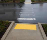 Rainy day cross walk with yellow traction pads royalty free stock images