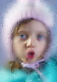 Rainy day - face of a little girl behind a dewy window Royalty Free Stock Photography