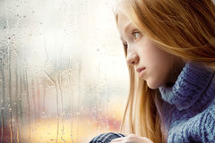 Rainy Day: Girl looking through the Window stock images