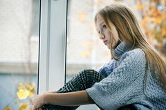 Rainy Day: Girl Sitting on the Window. Emotional Portrait of a sad Girl with long blonde Hair. She is Sitting on the Window in the Rainy Autumn Day Stock Photography