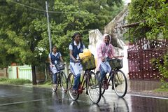 On a rainy day girls going to school on bicycles