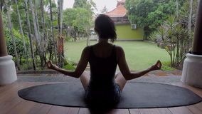 Rainy day on the island of Bali. The girl meditates in a pose of the yogi. The brunette relaxes and has a rest. Bali the stock video footage