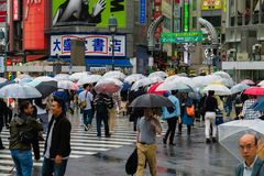 A rainy day in Japan showing people at the Shibuya Scramble crossing with umbrellas. Shibuya crossing is one of busiest places in Tokyo and is featured in many Stock Photos