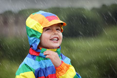 Rainy day. Little boy enjoying the rain dressed in a rainbow colored raincoat Stock Photos