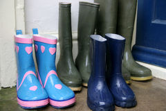 Rainy day out. Wet wellington boots in doorway Royalty Free Stock Photos