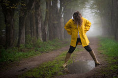 Rainy Day Puddle. Female with yellow raincoat looking at reflection in puddle conveying the feeling of playfulness, spontaneity and pensiveness royalty free stock image