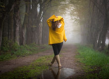 Rainy Day Raincoat hands up. Female with yellow raincoat hands up, contrasting gloomy background forest, pondering life, taking life slowly and enjoying nature Stock Images
