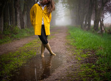 Rainy Day Reflection. Girl outside on a rainy foggy day. Stops by puddle which gives a sense of pensiveness and the ability to relax, slowdown and enjoy life royalty free stock photo