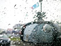 Rainy day on the road, Raindrops on car mirror with side wing mirror Royalty Free Stock Image