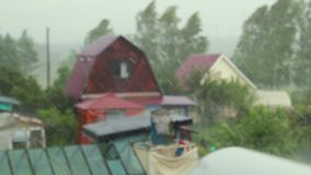 Rainy day scene, focus rain falling in sky with blur house background. Summer rain in the village, cloudy weather, raindrops falling on the houses stock video