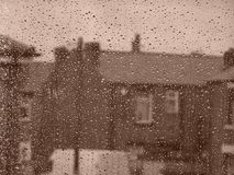 Rainy Day on the Street. A rainy day. Rain drops on a window against a quiet street outside. (Focus is on the raindrops royalty free stock image