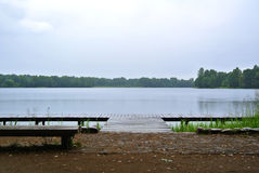 Rainy day at Trakai natural park, a view to a lake, forest, wooden bench and wooden quay. Lithuania Royalty Free Stock Photography