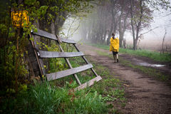 Rainy Day Walk. Female with yellow raincoat taking a leisure walk down country road on a misty rainy day.  Conveys sense of serenity, peacefulness, and Stock Photography
