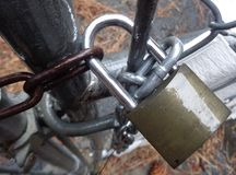 Rainy Day Wet Padlock on Chainlink Gate royalty free stock photography