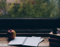 Rainy day by the window. With books, notepad and apple, nostalgic mood Royalty Free Stock Image