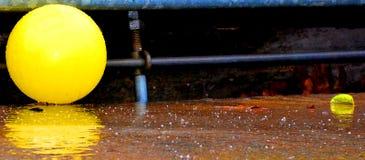 Rainy Day. Yellow Ball near stormdrain Royalty Free Stock Photos