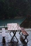 Rainy days. Wooden Bench Beside River Among Rain Royalty Free Stock Image