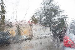 Rainy days, Evening, rain drops on the window with traffic blur. Blurry car silhouette. Autumn Abstract Backdrop royalty free stock images