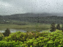 Rainy days. Looking through a rainy window at the great out doors on your holiday or vacation Stock Photography